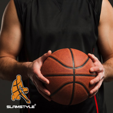A man in a basketball singlet holding a basketball