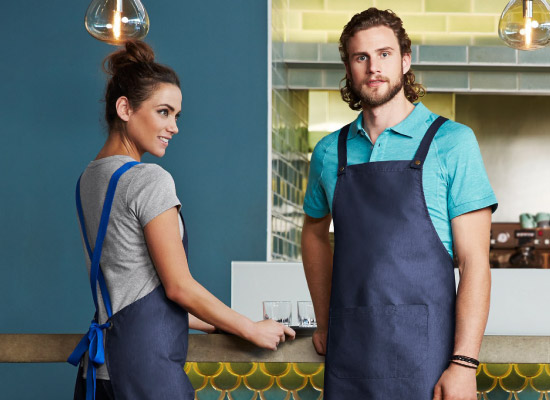 A waiter and waitress in custom uniforms including a classic hospitality apron.