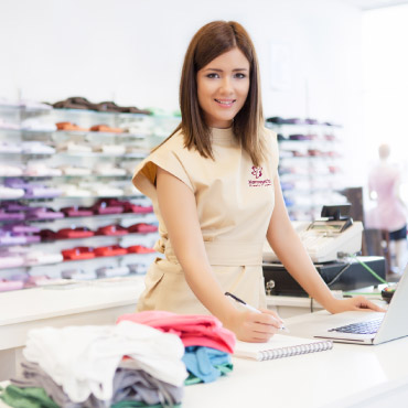 A retail worker wearing a smart-casual uniform.